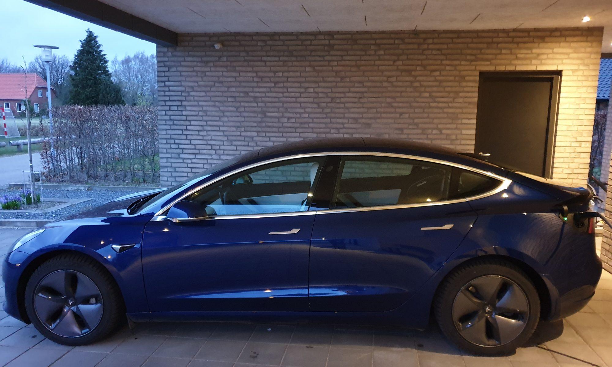 Blå Tesla Model 3 i garage